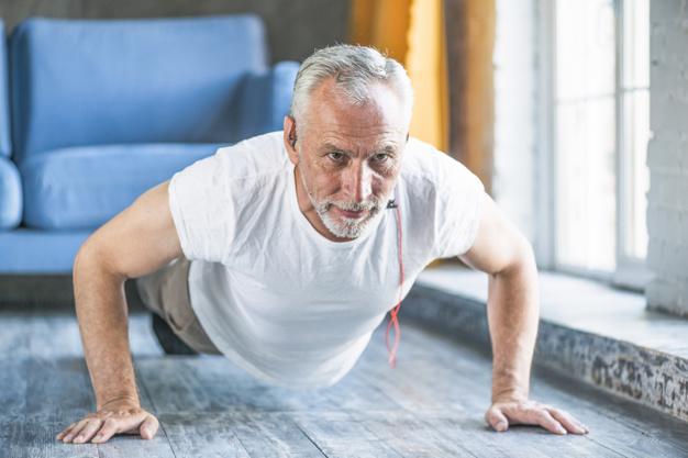 senior-man-doing-pushup-at-home_23-2147859867